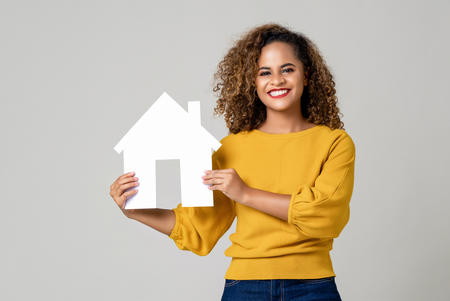 Bild vergrößern: Portrait of young happy smiling African American woman holding paper home for real estate concept