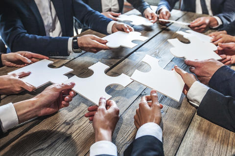 Bild vergrößern: Business people and puzzle on wooden table, teamwork concept