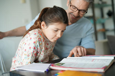 Bild vergrößern: Man helping daughter with homework
